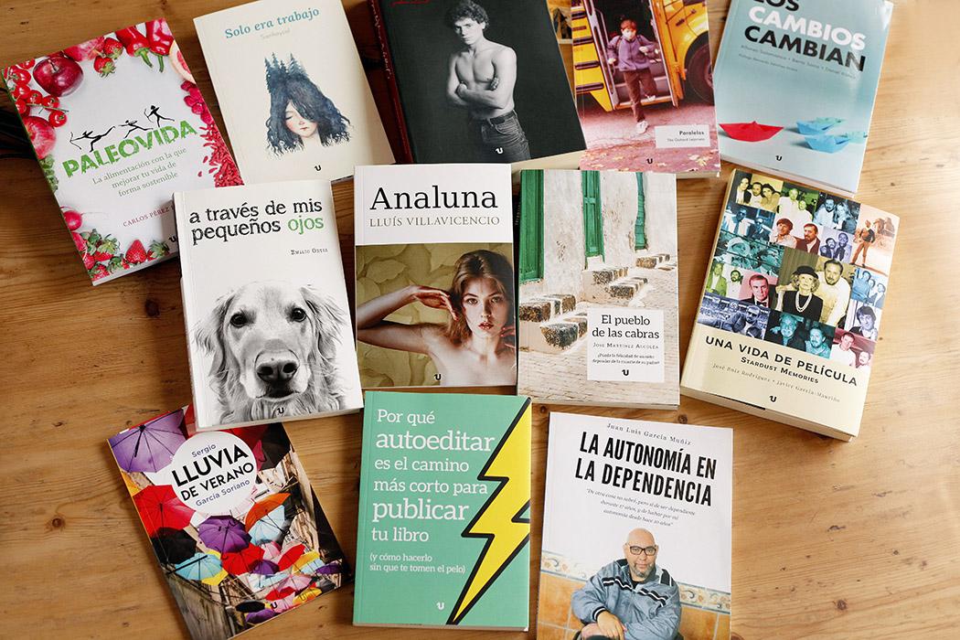 Foto de varios libros sobre una mesa. Todos tienen cubiertas en color plastificadas (algunos brillo y otros mate).