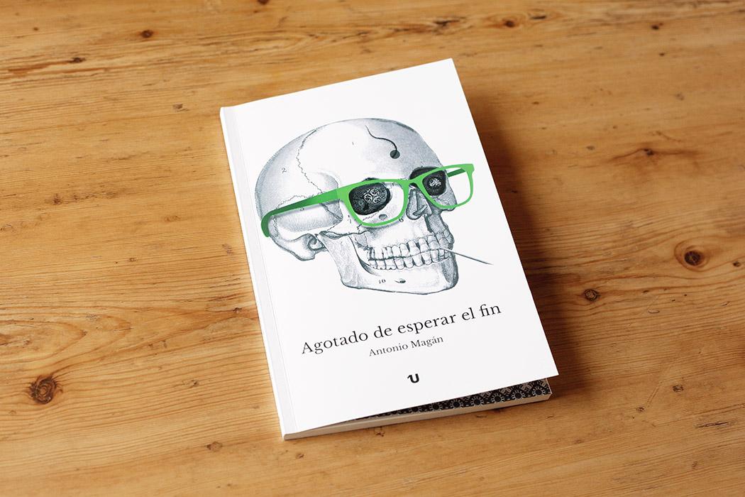 """Foto de la portada del libro """"Agotados de esperar el fin"""" de Antonio Magán. Consiste en una ilustración de una calavera con un palillo entre los dientes y unas gafas verde fósforito."""