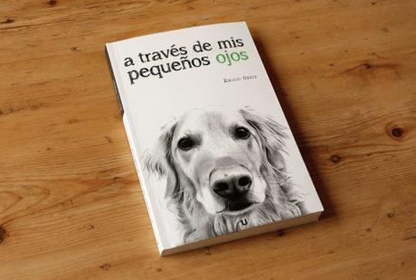 """Foto de la portada del libro """"A través de mis pequeños ojos"""" de Emilio Ortiz, en su primera edición. Muestra la ilustración en Blanco y Negro de la cara de un perro guía mirando fijamente a cámara."""