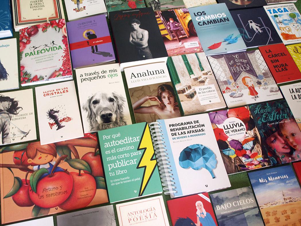 Foto de muchos libros de distintos tamaños sobre una mesa