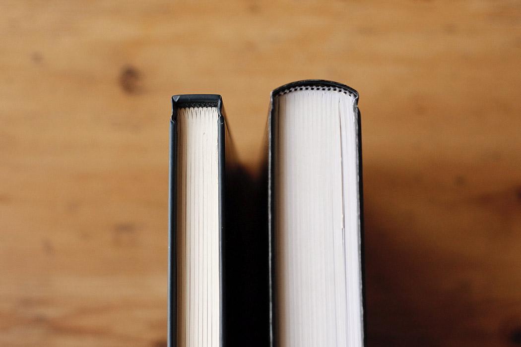 Foto de dos libros en tapa dura para apreciar la diferencia entre lomo recto y lomo redondo.