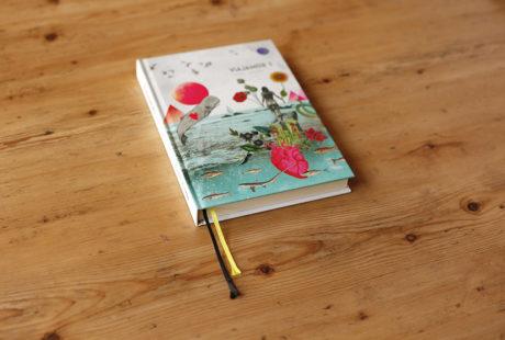 Foto de un libro en tapa dura al cromo, lomo cuadrado, con dos cintas de registro en amarillo y negro.
