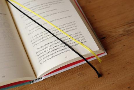 Foto del detalle de dos cintas de registro (amarilla y negra) en un libro abierto encuadernado en tapa dura.