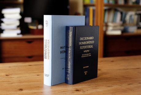 Foto de dos libros encuadernados en tapa dura guaflex: uno con pasta negra y letras doradas; otro con pasta azul celeste y letras negras.