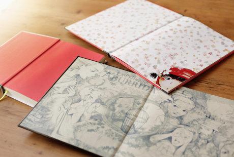 Foto de varios libros encuadernados en tapa dura con ejemplos de guardas: impresas en color, impresas en blanco y negro, sin imprimir (en papel rojo).