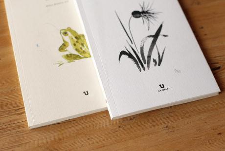 Detalle de dos libros con cubierta verjurado: uno en acabado crema y el otro en acabado blanco.