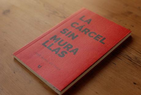 Foto de un libro con cubierta en verjurado impresa totalmente con fondo rojo y letras negras.