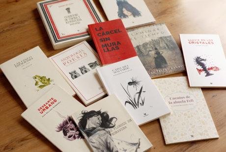 Foto de varios libros con cubierta verjurado en blanco, en crema y totalmente impresa (en rojo, en el ejemplo de la foto).